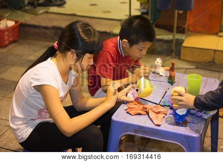 Hanoi, Vietnam - Nov 2, 2014: Children learn to paint plaster figurine by brush and color ink on Ma May street, quarter of Hanoi. Focus on the plaster figurine
