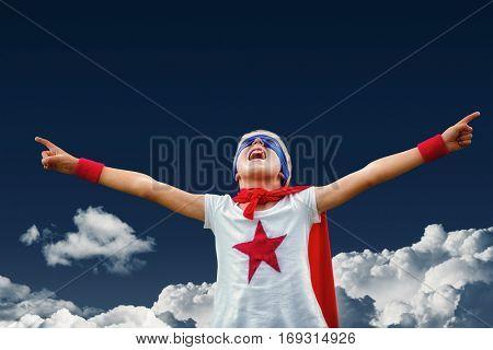 Little boy dressed as against navy sky