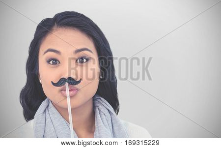 Pretty Asian woman with fake mustache posing for camera against white background with vignette