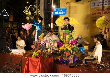 Hanoi, Vietnam - Nov 2, 2014: Vietnamese artists perform folk music and song on Ma May st, old town of Hanoi. The little child plays the Holy Mother. Focus man artist on the left