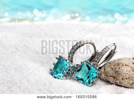 Jewelry earrings with aquamarine on sand beach background soft focus