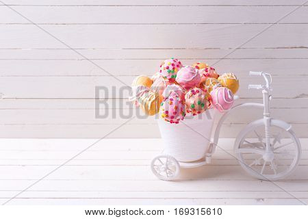 Cake pops in decorative bicycle on white wooden background. Selective focus. Place for text.