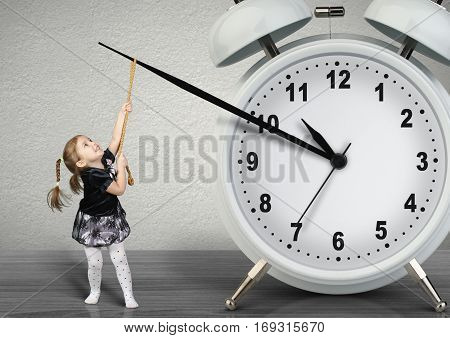 Little child girl pulling hand clock time management concept