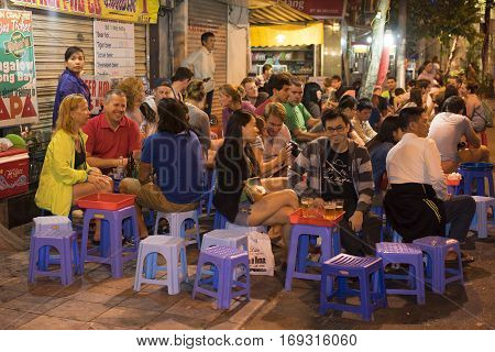 Hanoi, Vietnam - Nov 2, 2014: People drink beer on street at night in old quarter, center of Hanoi. Drinking beer on street is one of the most special culture of Hanoi.