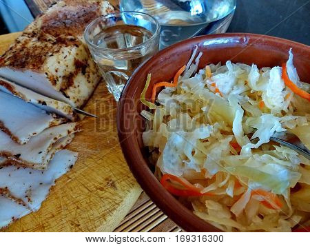 Sauerkraut in a clay bowl. Closeup. Sliced homemade lard with condiments. Carafe and a glass of vodka. Natural food, appetizer. Traditional Dishes of Russian Cuisine