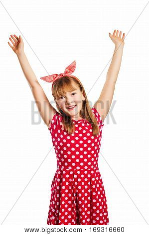Studio shot of young little 9-10 year old girl, wearing red polka dot dress and headband, isolated on white background, pin up style, arms wide open
