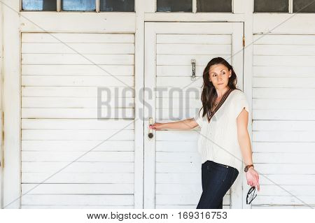 Outdoor fashion portrait of 35-40 year old woman wearing white marine pullover and dark denim jeans, holding sun-glasses, standing against white wooden background