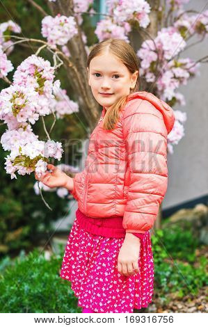 Spring portrait of a pretty little girl of 7 years old wearing coral jacket standing between branches of a blooming tree