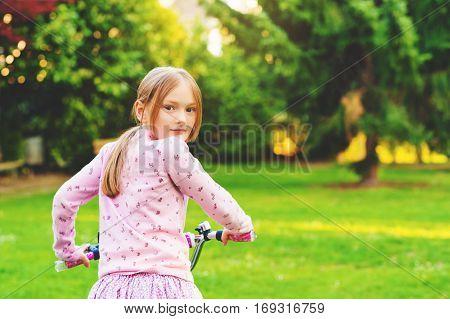 Little girl on bicycle in summer park, looking back over shoulder