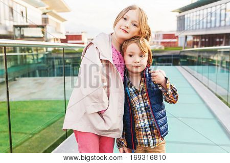 Outdoor portrait of two cute kids, little brother and big sister, boy and girl in a city, wearing spring jackets