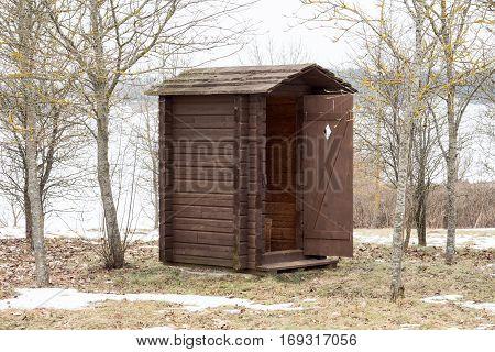 Wooden toilet with opened door in the park