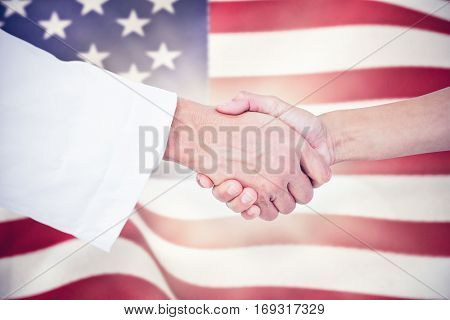 Extreme closeup of a doctor and patient shaking hands against digitally generated united states national flag