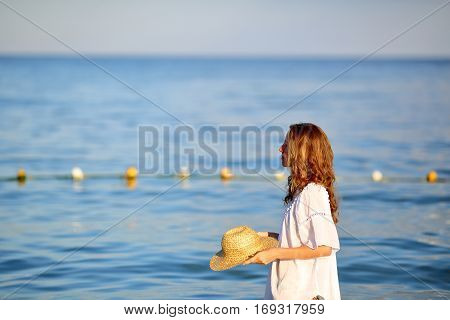 Woman In White Tunic And Straw Hat In Hands On The Beach