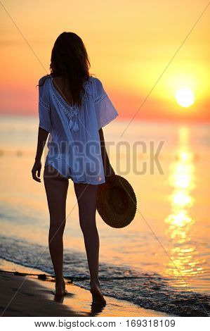 Sexy Woman Walking On The Beach At Sunrise
