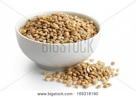 Dry Pearl Barley In White Ceramic Bowl Isolated On White. Spilled Barley.