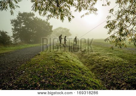 Three people walking on a foggy day. Taken in the autumn on a foggy but bright morning in October.
