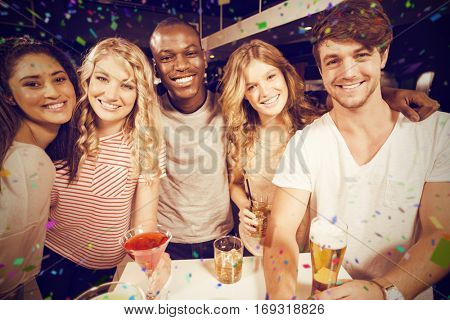 Portrait of happy friends with beer and cocktails on table against flying colours