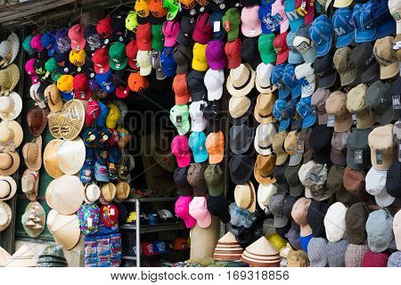 Hanoi, Vietnam - Nov 16, 2014: Bunch of different hats displayed for selling in a sidewalk hat store on Hang Bai street