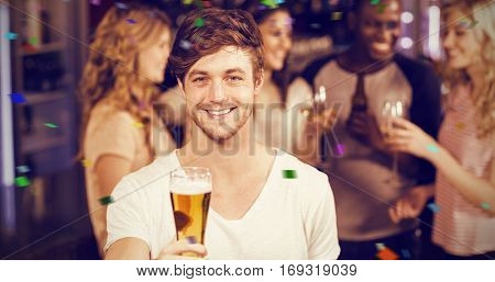 Smiling man showing beer with his friends against flying colours