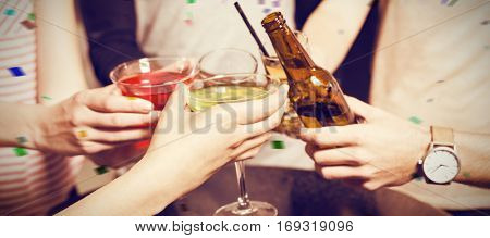 Cropped image of friends toasting with beer and cocktails against flying colours