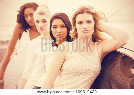 Portrait of female friends posing while leaning on limousine at outdoors
