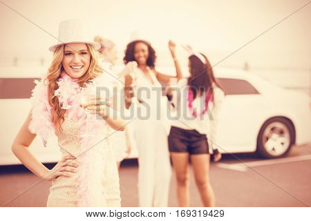 Women holding champagne next to limousine for night out party