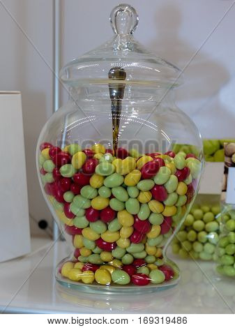 Green, Yellow And Red Sugared Almond In Glass Jars