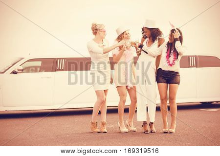 Frivolous women drinking champagne next limousine for night out