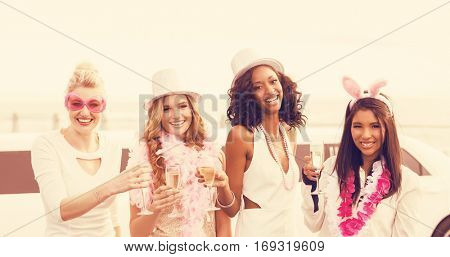 Portrait of women holding champagne flute while standing next to limousine