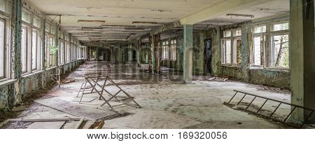 ruined abandoned school hall with debris and remains in Pripyat