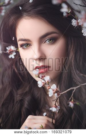 Sensual young woman portrait at blossoming tree in the garden. Beauty of woman and nature consept. Close-up face of beautiful model with curly brown hair posing and looking at camera.