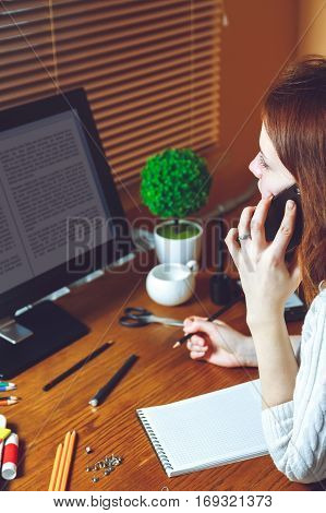 Young business woman talking on the phone while sitting at the table. Multitasking concept. Telework concept