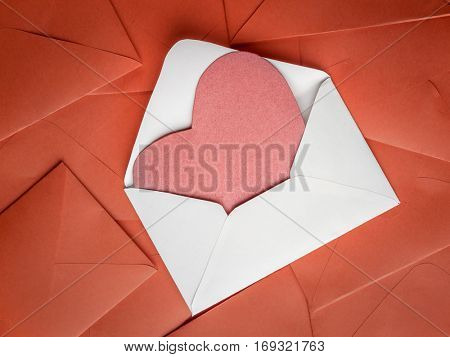 White envelope with red paper heart insert placed on pile of red envelopes