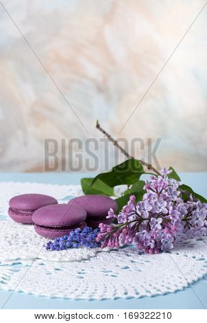Lilac flowers and purple French macaroons cookies on the table