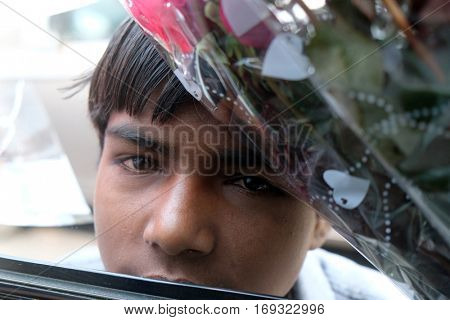 DELHI, INDIA - FEBRUARY 13 : A poor boy trying to sell flowers on the street of Delhi, India on February, 13, 2016.