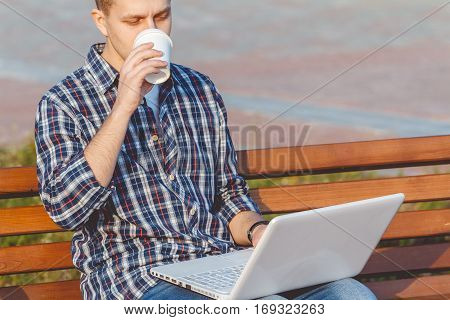 Young male businessman with the notebook. The concept of remote working outdoors