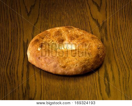 Rye bread on a wooden table. Top view. Fresh fragrant crispy bread.  Tandoor bread on cutting board closeup. Bread rye scone on an old background. Orient cuisine.