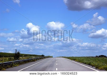 Paved road on the background of blue sky leaving for horizon.