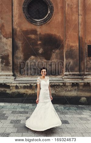 Bride whirls under black round window in the old city
