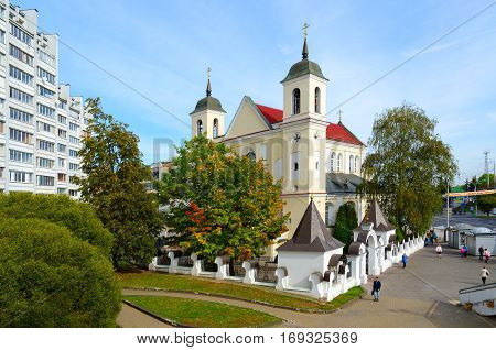 MINSK BELARUS - OCTOBER 1 2016: Unidentified people go on Street Rakovskaya near Saint Peter and Paul Cathedral (Cathedral of Holy Apostles Peter and Paul) Minsk Belarus