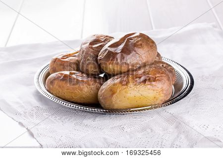 Baked potato on metal tray. Rustic style.