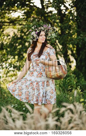 Portrait of pretty brunette woman with long hair and wrath of wildflowers on head holding basket in hand. Girl wearing dress in floral print walking in meadow looking away. Warm summer day.