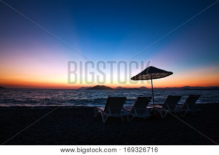 Sun loungers on the beach on a background of a beautiful dawn sky