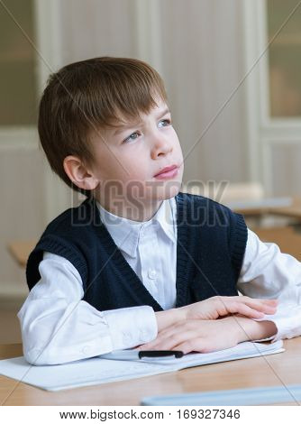 Diligent preschool sitting at desk  in classroom