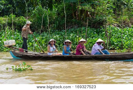 An Giang, Vietnam - Nov 29, 2014: Tourism rowing boat carries tourists wearing Vietnamese conical hat on Tien river, Mekong delta, southern Vietnam
