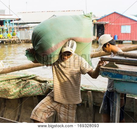 An Giang, Vietnam - Nov 29, 2014: Worker carries heavy bag of fish food from small wooden transportation boat to floating fish farm in Mekong delta
