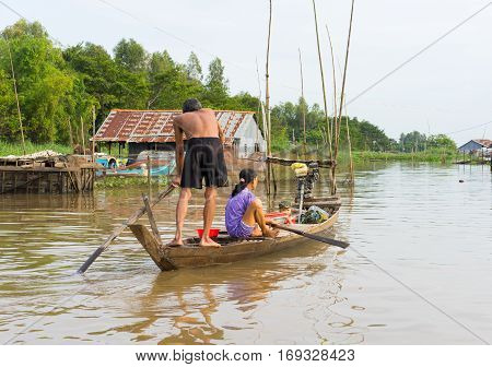 An Giang, Vietnam - Nov 29, 2014: A family moving by rowing boat, the most common transportation mean of rural people in Mekong delta, southern Vietnam