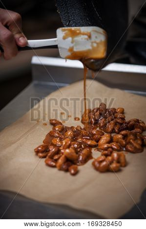 Almond caramel cooking. Preparing nuts on pan with sugar for dessert
