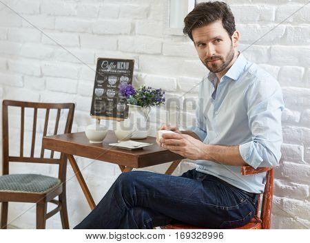 Young man sitting at coffee table holding cup, looking left.