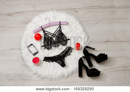 Fashionable concept a set of lacy underwear phone shoes and red candles on the white fur. Top view space for text